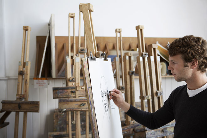 art student using an easel in an art school classroom